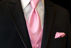 Pink tie, vest and handkerchief accenting a black tuxedo.