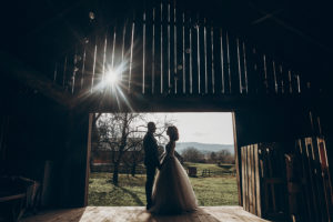 stylish bride and groom hugging in sun light on background of wooden wall in barn. rustic wedding concept space for text. happy bohemian newlyweds family couple embracing