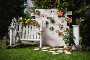 Wedding party. Beautiful unusual wedding decor. Rustic Style. Bench wall of flowers lanterns at the rustic wedding photo zone. Wedding concept